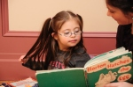 child with Down syndrome reading