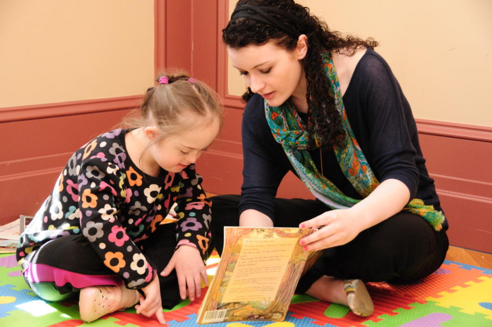 Child with Down syndrome reading with teacher