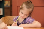 child with Down syndrome writing
