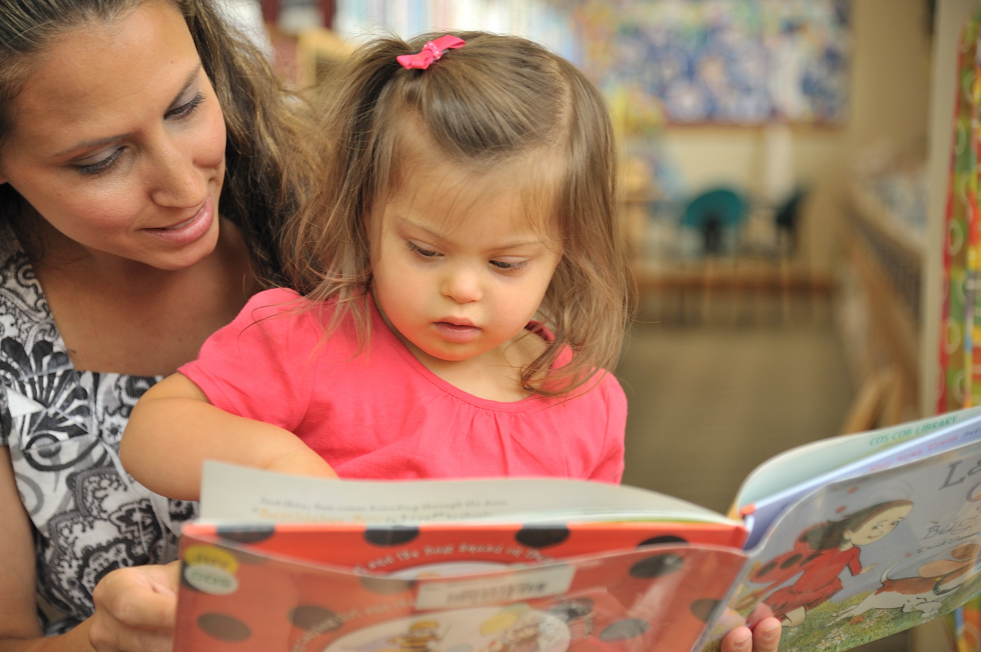 child with Down syndrome reading with mother